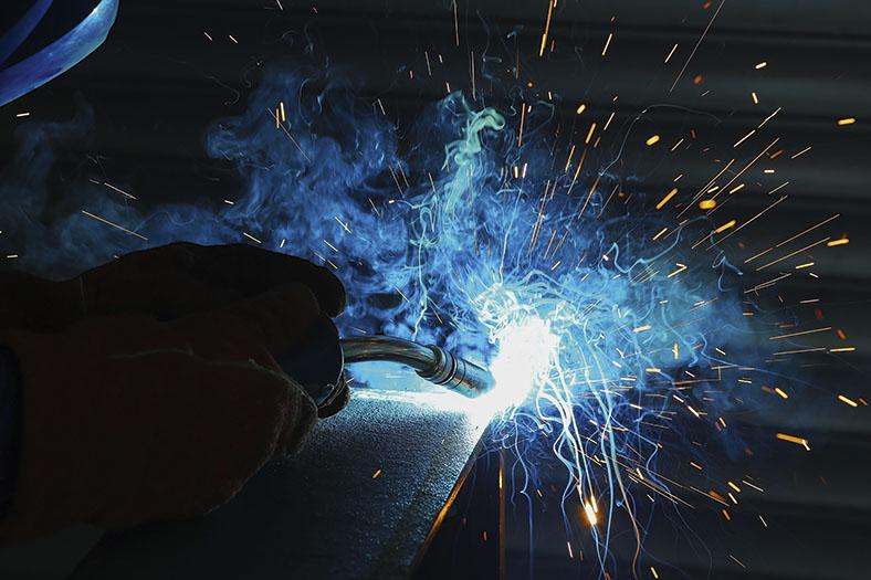 Arbeiter in Handschuhen bearbeitet mit einem MIG-Gaschweißgerät einen Stahlträger, sichtbar sind der Schweißlichtbogen und sprühende Funken.