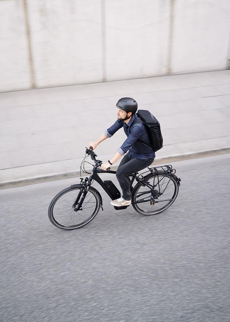Ein Radfahrer in Jeanshose und -hemd mit schwarzem Fahrradhelm und Rucksack fährt auf einem schwarzen Fahrrad eine leere Straße entlang, Ansicht von schräg oben.