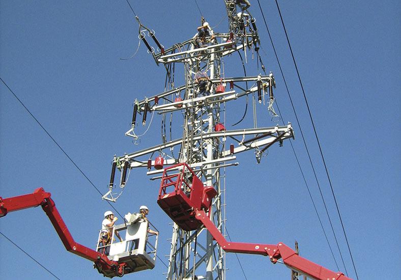Zwei rote Krankörbe und die Spitze eines Hochspannungsmastes vor blauem Himmel. In einem Korb befinden sich zwei Elektrofachkräfte mit Schutzhelmen.