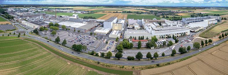 Luftbild des deutschen Sitzes des norwegischen Aluminiumherstellers Hydro Aluminum Rolled Products GmbH in Grevenbroich. Man sieht verschiedene Fabrikgebäude und Parkplätze, im Vordergrund eine Straße und umliegende Felder.