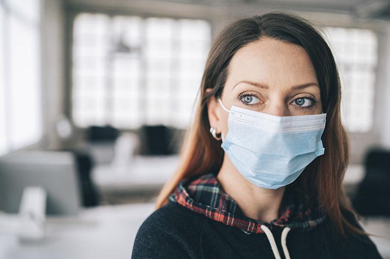 Frau mit langen braunen Haaren mit einer hellblauen Atemschutzmaske. Sie trägt ein dunkles Sweatshirt mit rot karierter Kapuze