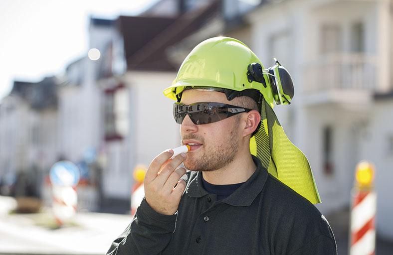 Arbeiter mit Schutzhelm und Nackenschutz steht draußen im Sonnenschein, er trägt eine Sonnenbrille und trägt mit einem Lippenstift UV-Schutzmittel auf.