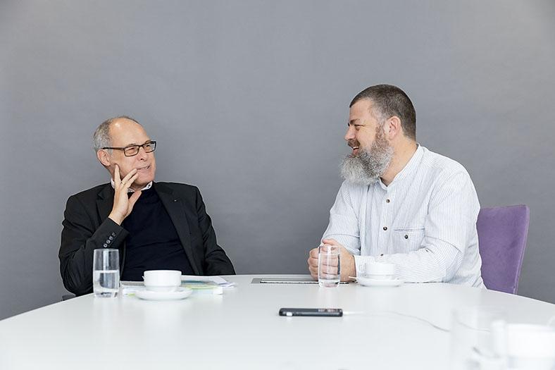 BG ETEM-Arbeitspychologe Just Mields (links mit Brille, in dunklem Pullover und Jackett) und Unternehmensberater Haeme Ulrich (rechts in weißem Hemd mit Vollbart) sitzen an einem Tisch mit Wassergläsern und Kaffeetassen und unterhalten sich über agiles Mindset.