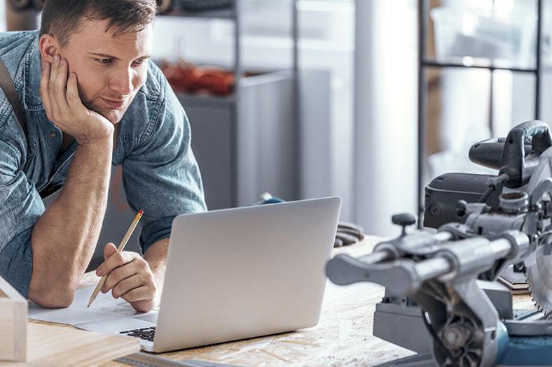 Handwerker mit Bleistift stützt sich mit einem Arm auf einen Tisch und beugt sich zu einem Laptopbildschirm. Auf dem Tisch hinter dem Laptop steht ein Maschinenteil.