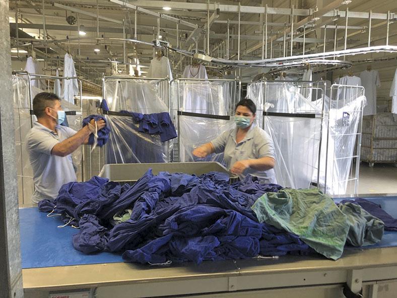 Eine Mitarbeiterin und ein Mitarbeiter der Firma Bardusch Textil Mietdienste GmbH in Augsburg sortieren dunkelblaue Textilien auf einem Tisch. Beide tragen einen Mund-Nasen-Schutz.