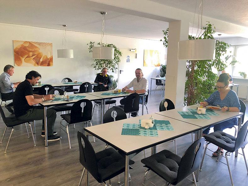 Kantine der Firma Topp Textil GmbH in Durach, mehrere Mitarbeiterinnen und Mitarbeiter sitzen mit großen Abstand an den Tischen, es ist ein Mindestabstand von 1,50 m einzuhalten.