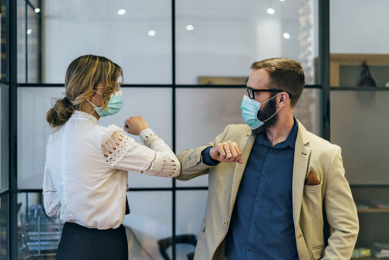 Kollegin in weißer Bluse und Kollege in heller Anzugjacke und dunkelblauem Hemd im Büro begrüßen sich durch Berührung der Ellenbogen. Beide tragen eine hellblaue Atemschutzmaske.