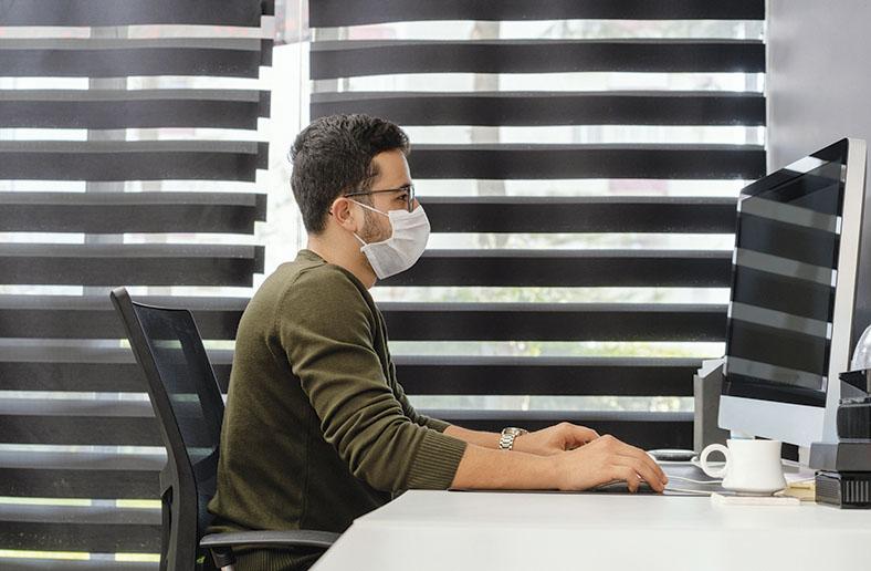 Profilansicht eines Mannes an einem Schreibtisch. Er sitzt vor einem Computerbildschirm und bedient Computermaus und Tastatur. Er trägt einen braunen Pullover, eine Brille und einen weißen Mund-Nasen-Schutz als Corona-Arbeitsschutzmaßnahme.