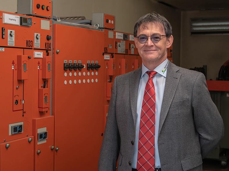 Ein Mann steht rechts neben einer orangenen Mittelspannungs-Schaltanlage. Er hat kurzes graues Haar, trägt eine Brille und einen grauen Anzug mit roter Krawatte.