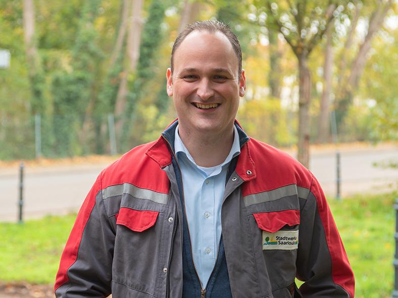 Ein Mann steht im Freien mit Bäumen und Wiese im Hintergrund und lächelt in die Kamera. Er hat kurzes braunes Haar, trägt eine rot-graue Arbeitsjacke mit Logo der Stadtwerke Saarlouis und ein hellblaues Hemd.