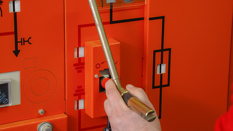 Auf dem Bild ist eine elektrische Schaltanlage in orange zu sehen. Eine Hand dreht mit einem Stiftschlüssel an einem Entriegelungskästchen.