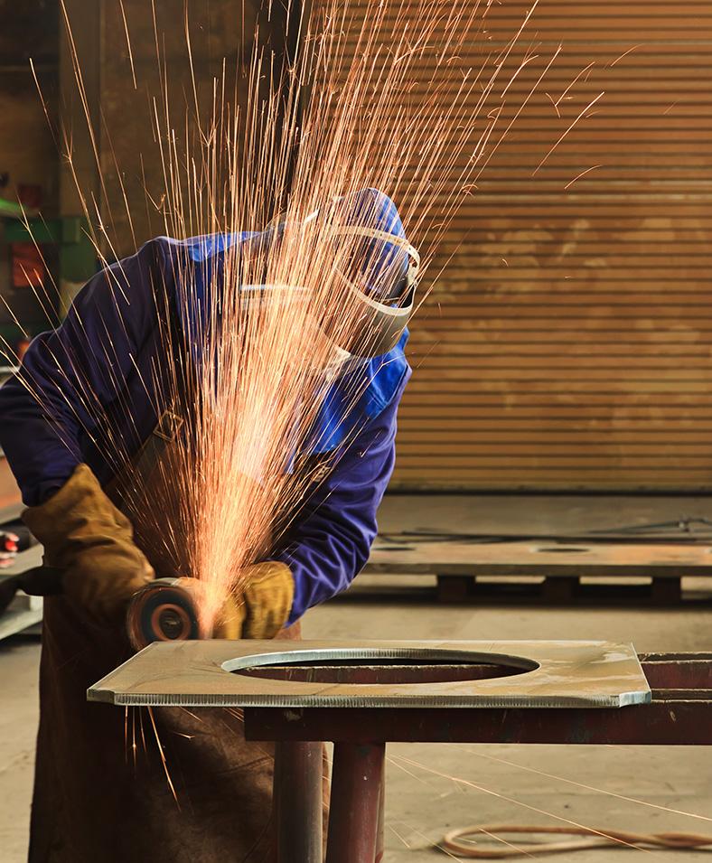 Beschäftigter schleift an einem Werkstück aus Stahl. Er trägt Schutzkleidung und Maske, um sich vor Schleifstaub und Funkenflug zu schützen.