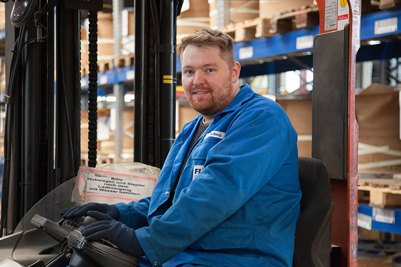 Maschinen- und Anlagenführer Christian Marcus steht in blauer Arbeitskleidung in einer Lagerhalle mit Drahtspulen.