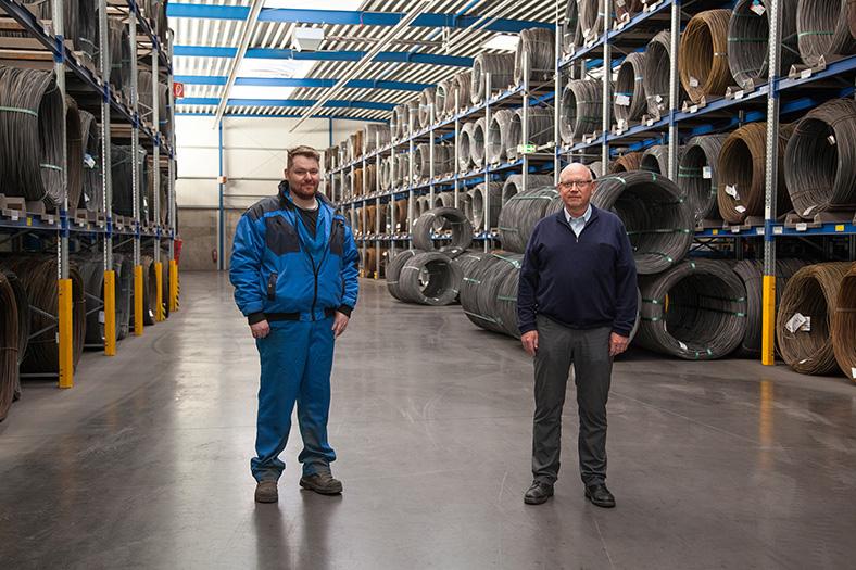 Maschinen- und Anlagenführer Christian Marcus und technischer Leiter Albrecht Borner stehen nebeneinander in einer Lagerhalle mit Regalen voller Drahtspulen.