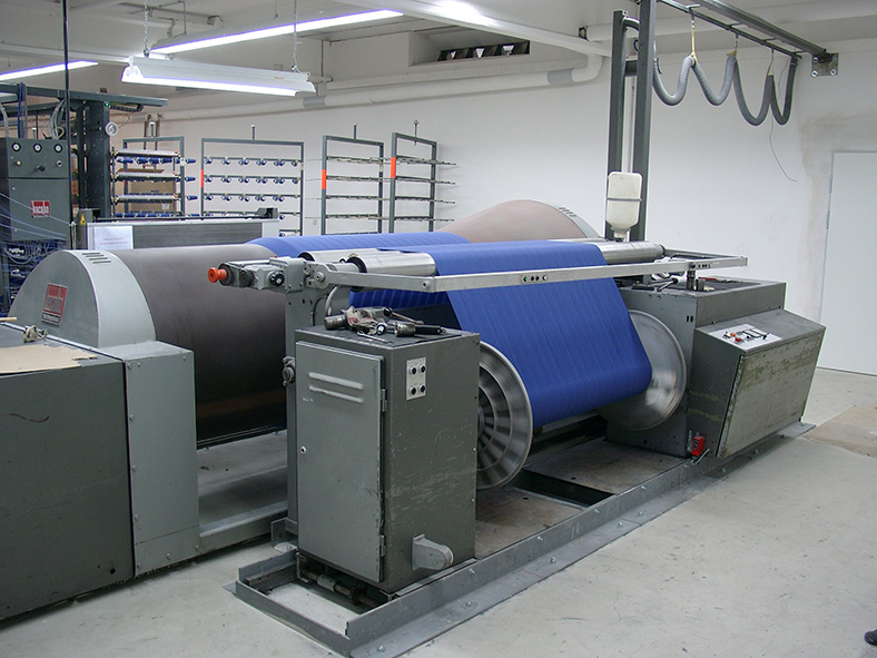 Konusschärmaschine in einer Werkshalle. Die Walzen der Maschine sind mit blauem Stoff umwickelt.