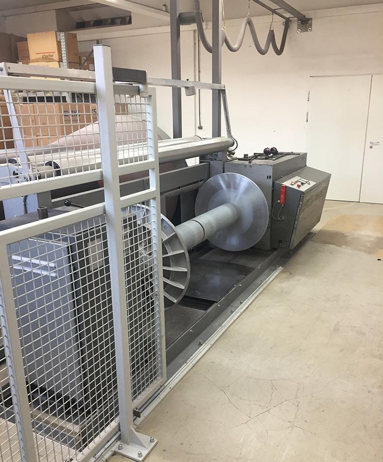 Konusschärmaschine in einer Fabrikhalle mit nachgerüstetem Schutzgitter in offener Position.