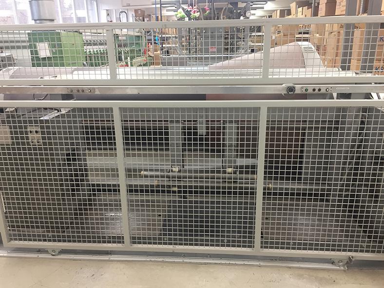 Konusschärmaschine in einer Fabrikhalle mit geschlossenem Schutzgitter.