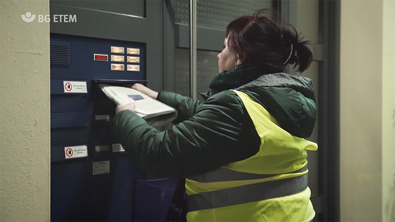 Zeitungszustellerin wirft im Dunkeln Post in einen Briefkasten ein.
