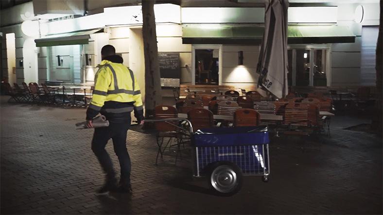Zeitungszusteller zieht einen Fahrradanhänger bei Dunkelheit zu seinem Zustellfahrrad.
