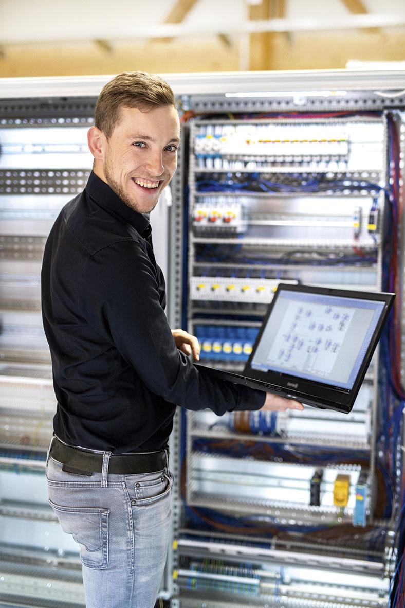 Niklas Schmidt, Elektromeister der GfG in Aichach, steht vor einem Schaltschrank. Er hält ein Tablet mit einem Arbeitssicherheit-Schaubild vor sich.