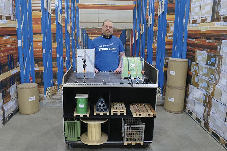 Ausschnittsbild des Erklär-Videos zum Thema Ladungssicherung zeigt den Moderator in blauem T-Shirt, vor sich ein Tisch mit unterschiedlichen Demonstrationen von Ladungssicherungsarten.