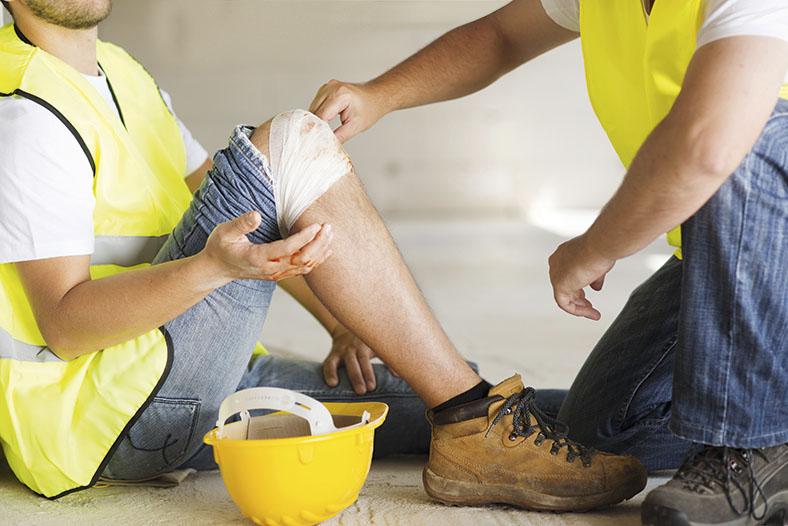 Ein Bauarbeiter mit gelber Warnweste und einer einbandagierten Wunde am Knie sitzt auf dem Boden. Ein weiterer Bauarbeiter kniet vor ihm und versorgt die Wunde.