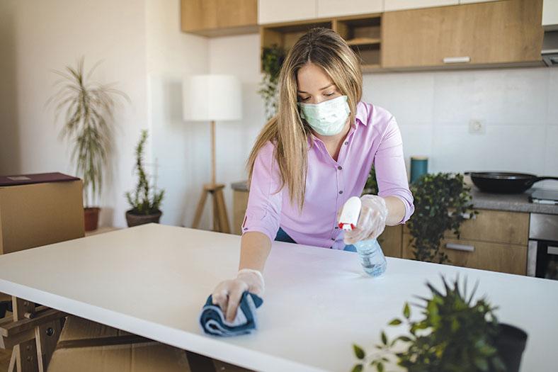 Junge weibliche Haushaltshilfe in Privathaushalt reinigt einen Tisch. Sie trägt eine Atemschutzmaske, die ihr vom Arbeitgeber als Ausrüstung zur Verfügung gestellt wurde.