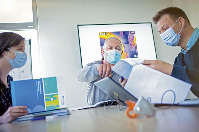 Teambesprechung der STB Sachsenwind über Arbeitssicherheit in einem Konferenzraum mit mehreren Personen, die Mund-Nasen-Schutz tragen.