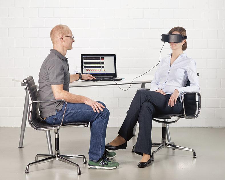 Pupillographischer Schläfrigkeitstest mit einem Testleiter und einer weiblichen Testperson, die eine an ein Notebook angeschlossene Maske auf den Augen trägt.