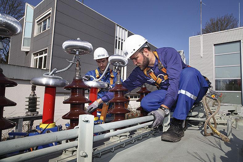 Zwei Facharbeiter mit weißen Schutzhelmen, blauer Arbeitskleidung und Schutzausrüsteng arbeiten auf einem Gebäudedach.