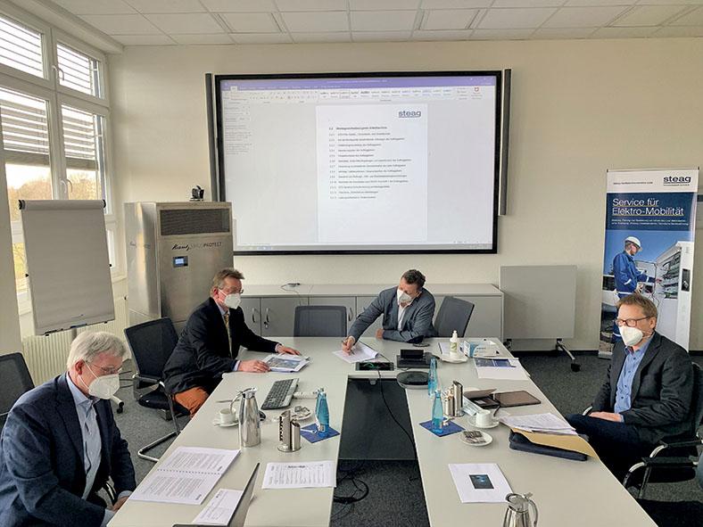 Besprechung zur Betriebssicherheit zwischen vier männlichen Personen in Anzügen, die um einen Konferenztisch sitzen. Im Hintergrund unterhalten sich STS-Geschäftsführungsmitglied Rainer Borgmann und BG Aufsichtsperson Bernhard Beckmann. Alle tragen FFP2-Masken.