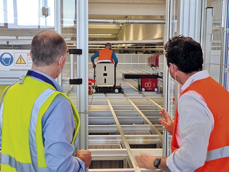 Szene Störungsbeseitigung Roboter in einem Ersatzteillager durch einen Mitarbeiter, Fachkraft für Arbeitssicherheit der SIG GmbH (l.) und BG-Aufsichtsperson Martin Jilko stehen im Vordergrund mit Sicherheitswesten bekleidet und schauen zu.
