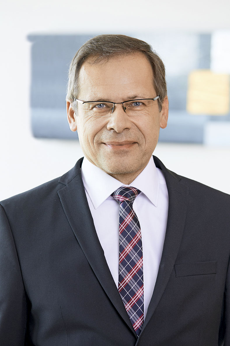 Das Porträtfoto zeigt Johannes Tichi, Vorsitzender der Geschäftsführung der BG ETEM. Er hat kurze Haare und trägt eine Brille. Er trägt ein dunkles Jackett, ein weißes Hemd und eine blau gestreifte Krawatte.