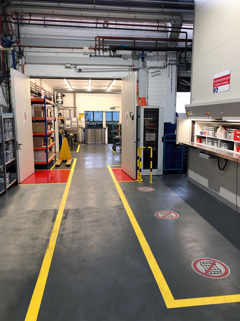Auf dem Foto sieht man den gelb begrenzten Fluchtweg in einer Werkshalle, seitlich stehen diverse Gegenstände. Weiter hinten im Bild sieht man rote Felder auf dem Boden im Öffnungsbereich von Brandschutztüren.