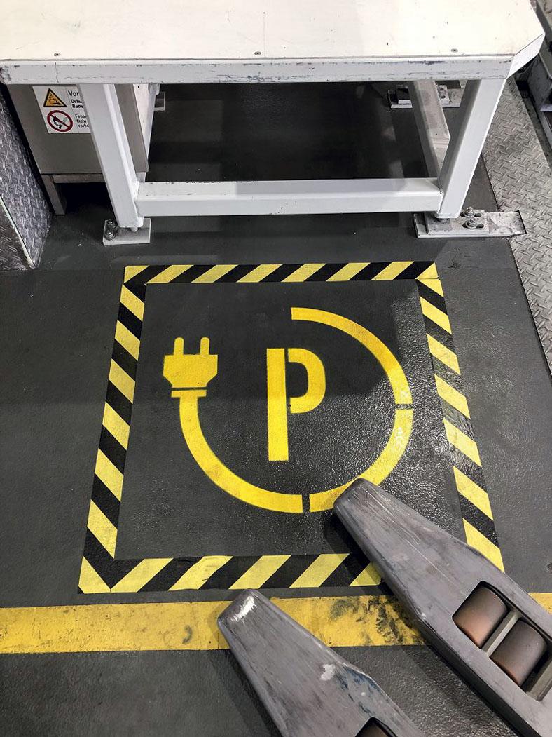 Ansicht von oben auf den grauen Bodens einer Werkshalle. Ein quadratischer Teil des Bodens ist gelb-schwarz markiert mit dem Buchstaben P und einem umlaufenden Stromkabel mit Stecker als Parkplatz für elektrische Ladevorgänge. Man erkennt rechts im Vordergrund Teile eines Gabelstaplers.