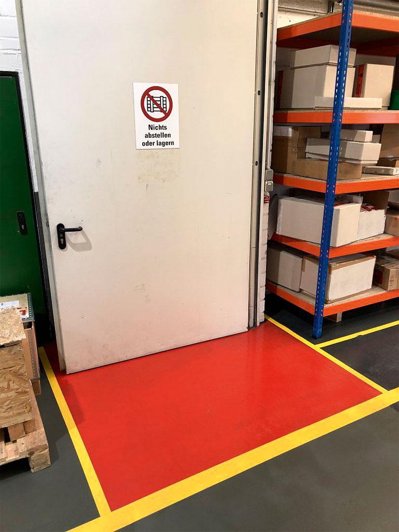 """Auf dem Foto sieht man eine offen stehende Brandschutztür mit einem Warnschild, auf dem """"Nichts abstellen oder lagern"""" steht. Im Öffnungsbereich der Tür ist der Boden rot bemalt. Auf der rechten Seite sieht man ein Regal mit Kartons."""