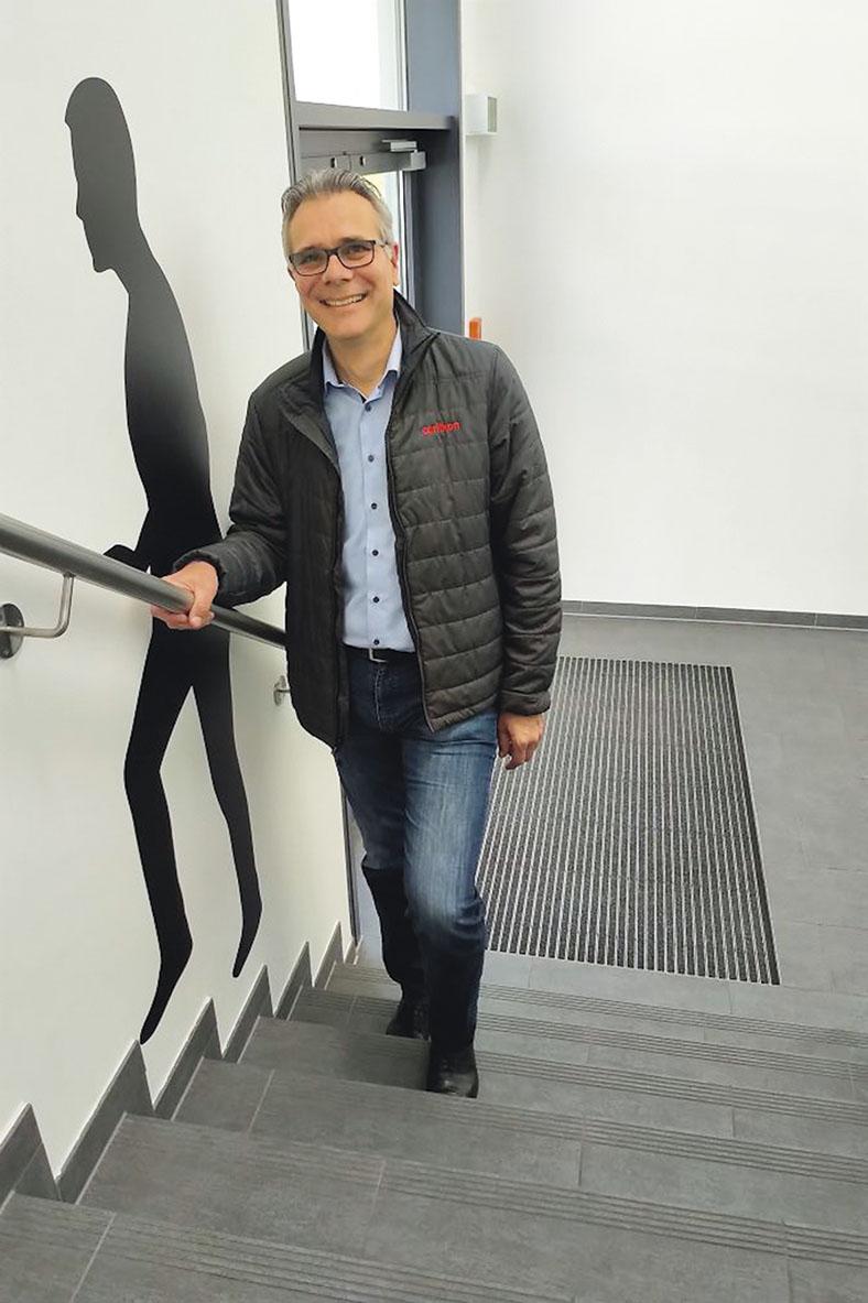 Das Foto zeigt Michael Ribbe, der in einem Treppenhaus eine Treppe heraufsteigt mit einer Hand am Handlauf. Er hat kurze Haare, trägt eine Brille, eine offene schwarze Steppjacke, ein blaues Hemd und Jeans. Er lächelt in die Kamera.