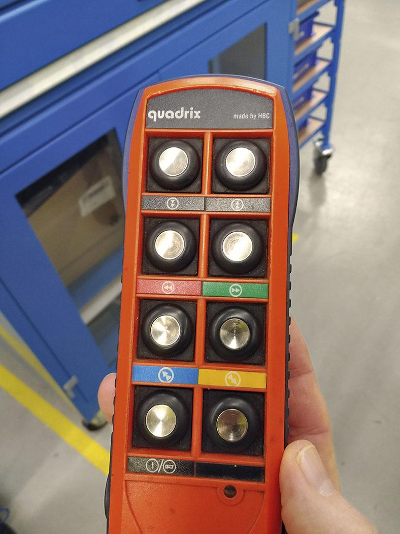 Auf dem Foto sieht man eine eine Hand, die eine Funkfernsteuerung für einen Kran in orange mit mehreren Bedienknöpfen hält.