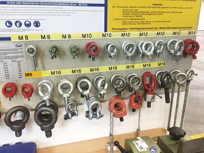 Das Bild zeigt ein Aufbewahrungswand mit beschrifteten Haken, an denen Lastböcke, Ringschrauben und Schäkel zur Lastaufnahme in schwarz, rot und metallfarben hängen.