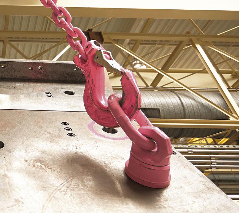 Das Bild zeigt in einer Fabrikhalle einen großen roten Lasthaken an einer Kette, der in die rote Metallschlaufe eines Lastbockes eingehängt ist, welcher an einer schrägen Metallplatte angebracht ist.