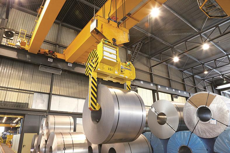 Auf dem Foto ist eine Fabrikhalle zu erkennen, in der ein großer orangener Brückenkran mit einer schwarz-gelb gestreiften Lasttraverse einen von mehreren metallfarbenen Zylindern transportiert.