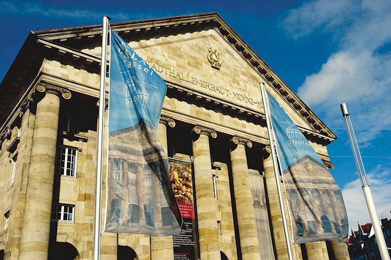 Das Bild zeigt die Front des Kongress Palais in Kassel mit Säulenportikus vor einem blauen Himmel. Im Vordergrund zwei Stangen mit wehenden blauen Fahnen, die Abbildungen der Stadthalle zeigen.