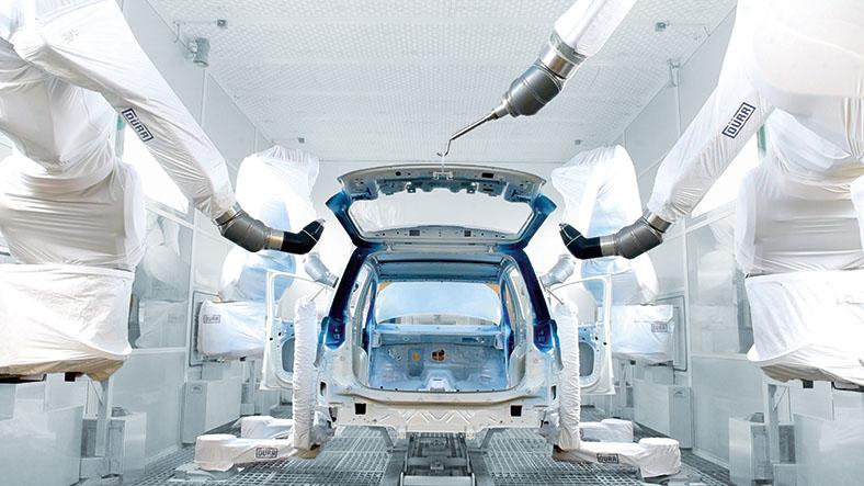 Das Foto ziegt den hinteren Teil einer Autokarosserie mit geöffneter Heckklappe, die in einer Werkshalle von Roboterarmen montiert wird. Die Roboter sind mit weißen Stoffen verkleidet.