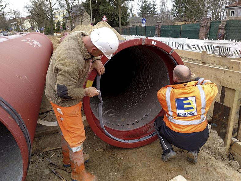 Auf dem Bild sind zwei Arbeiter zu sehen, links ein stehender Mann mit weißem Schutzhelm, rechts ein Mann in der Hocke. Sie montieren einen Dichtungsring an einem roten Abwasserrohr.
