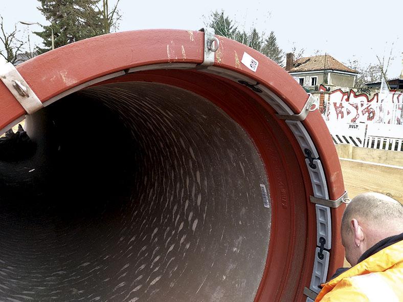 Das Bild zeigt Klammern zur Fixierung des Dichtrings an einem roten Abwasserrohr.