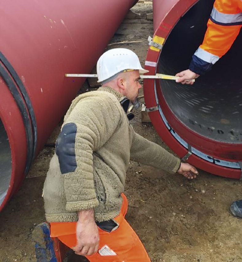 Auf dem Bild kniet ein Arbeiter mit weißem Schutzhelm vor zwei roten Abwasserrohren, daneben sieht man den Arm eines anderen Arbeiters, der mit einem Meterstab den Abstand zwischen zwei Rohren misst.