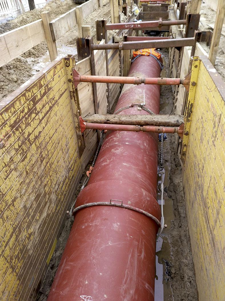Das Bild zeigt einen offenen Graben mit einer roten Abwasserrohrleitung, die durch Kettenzüge zusammengezogen ist. Der Graben ist durch Montagestangen abgestützt.