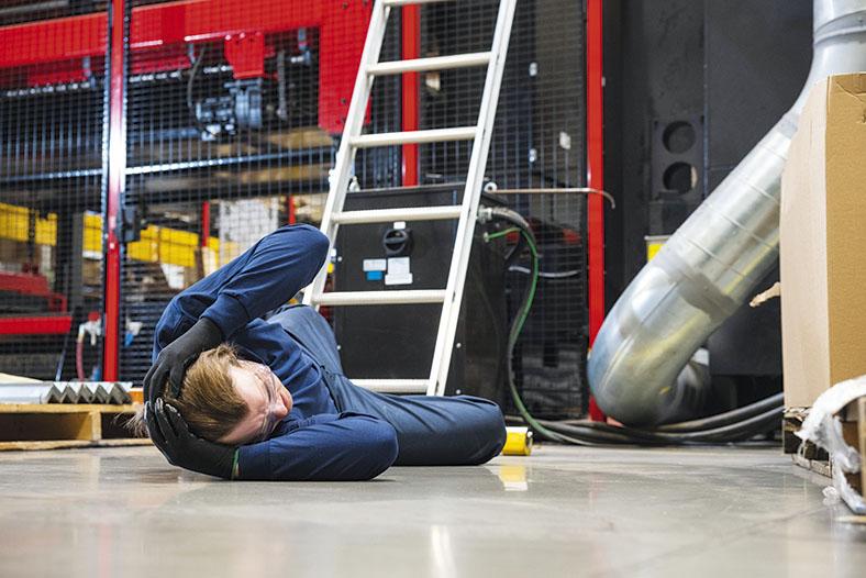 Die Abbildung zeigt einen Lagerraum mit einer Leiter. Auf dem Boden vor der Leiter liegt ein Mann in blauer Arbeitskleidung mit Schutzbrille und Handschuhen, der sich mit beiden Händen den Hinterkopf hält.