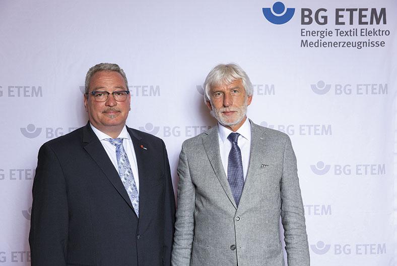 Das Bild zeigt von links nach rechts die Vorsitzenden des BG ETEM-Vorstands, Hans-Peter Kern und Dr. Bernhard Ascherl. Sie tragen beide einen Anzug und stehen nebeneinander vor einer BG ETEM Stellwand.