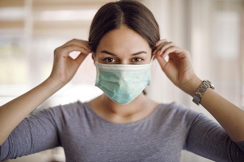 Das Bild zeigt das Porträt einer jungen Frau mit dunklen, zurückgebundenen Haaren in einem grauen Oberteil. Sie greift mit beiden Händen an die Haltegummis des Mund-Nasenschutzes, der ihre untere Gesichtshälfte bedeckt.